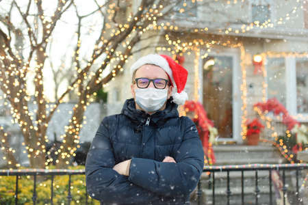 Mature man wearing face mask and Santa hat stand near his decorated home. Happy owner decorated his house and yard with garlands for Christmas and New Year.