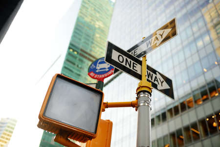 Different road signs with skyscrapers on background in New York City, USA. Traffic sign