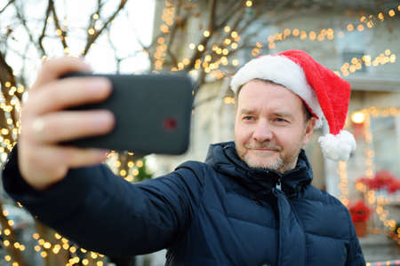 Mature man wearing Santa hat making selfie near his decorated home. Happy owner decorated his house and yard with garlands for Christmas and New Year. 免版税图像