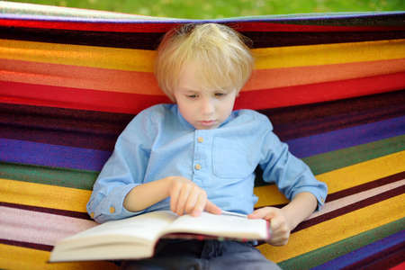 Cute little blond caucasian boy reading book and having fun with multicolored hammock in backyard or outdoor playground. Summer active leisure for kids. Child swinging and relaxing in hammock.