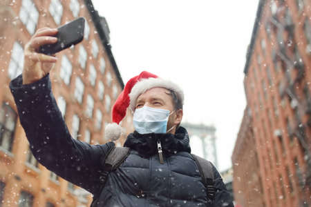 Middle aged man tourist wearing protective face mask takes selfie on street near the Manhattan Bridge in New York City on Christmas Eve. Winter holidays in NYC. New Year vacations in NYC. 免版税图像