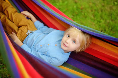 Cute little blond caucasian boy having fun with multicolored hammock in backyard or outdoor playground. Summer outdoors active leisure for kids. Child relaxing and swinging in hammock.