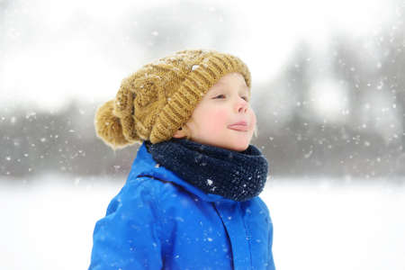 Cute child wearing a warm hat catching snowflakes with his tongue. Funny little boy in blue winter clothes walks during a snowfall. Outdoors winter activities for kids.