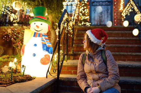 Young woman looking on house decorated for Christmas and New Year with glowing garlands in the Dyker Heights neighborhood, New York, USA. Evening magical vibe on Xmas eve in NYC.
