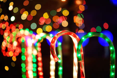 Close-up photo of Christmas and New Year decorations. Fence decorated with a garland like multicolored candy stick cane. Stylish outdoor Xmas decorations 免版税图像