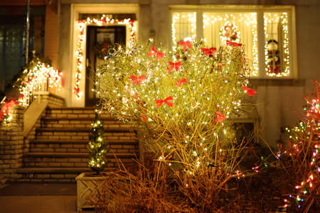 Magically decorated courtyard, staircase and house for the Christmas and New Year holidays. Glowing garlands twinkle beautifully in the evening. Typical street decoration for winter holidays in a small town in the USA. 免版税图像
