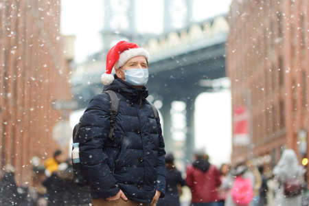 Middle aged man tourist wearing protective face mask is walking during a snowfall near Manhattan Bridge in New York on a snowy Christmas Eve. Winter Xmas holidays in NY. New Year vacations in NYC.