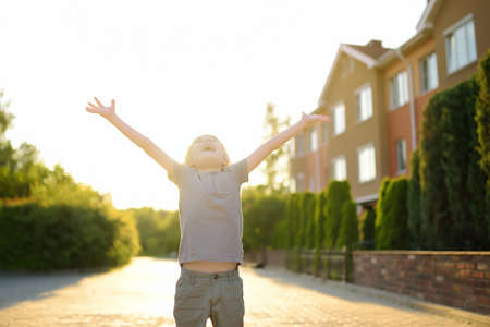 Cheerful little boy enjoying warm sunny summer day. Active child playing on the street of small town. Freedom, rest, vacation and childhood concept. Happy kid outdoors.
