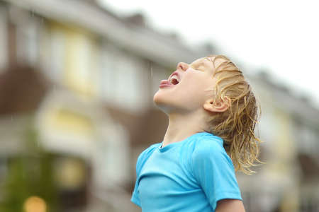 Little boy walking on rainy summer day in small town. Child having fun. Kid catches raindrops with tongue. Outdoors games for children in rain.