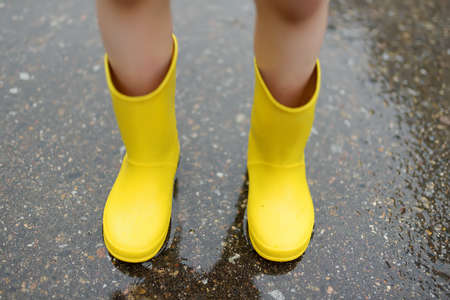 Little boy wearing yellow rubber boots walking on rainy summer day in small town. Child having fun. Outdoors games for children in rain.