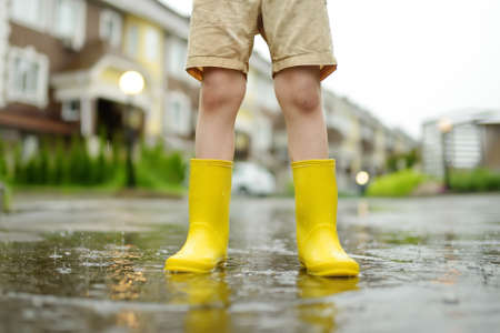 Little boy wearing yellow rubber boots walking on rainy summer day in small town. Child having fun. Outdoors games for children in rain. 版權商用圖片