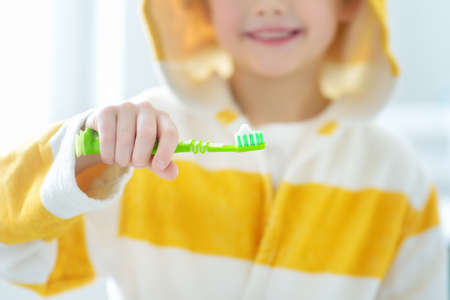 Preschooler boy cleaned teeth with dental floss and then is brushing his teeth with toothbrush. Learning children proper oral hygiene. Dental medicine and healthcare for kids.