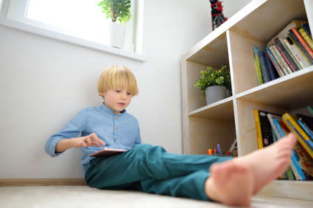 Preschooler boy watches cartoon movie by tablet or playing pc game. Overuse and addiction kids from gadgets. Digital device addiction. Stockfoto