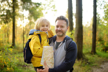 Schoolchild and his mature father hiking together and exploring nature. Boy with dad spend quality family time together in sunny forest. Adventure, scouting, orienteering and hiking tourism for kids.