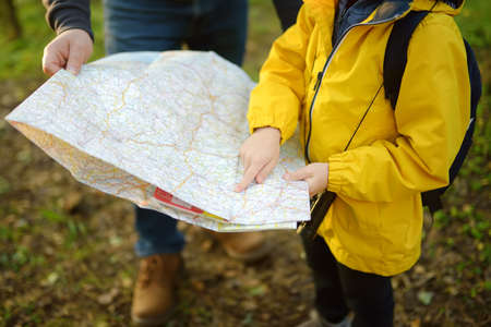 Schoolchild and his mature father hiking together and exploring nature. Little boy with dad looking map during orienteering in forest. Adventure, scouting and hiking tourism for kids. Daddy and son Stockfoto
