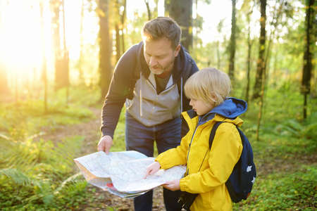 Schoolchild and his mature father hiking together and exploring nature. Little boy with dad looking map during orienteering in forest. Adventure, scouting and hiking tourism for kids. Daddy and son