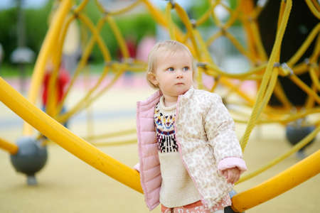 Cute toddler baby having fun on outdoor playground. Kindergarten, daycare, nursery for small children. Equipment for playground and entertainment park for active leisure for family with kids. Stockfoto
