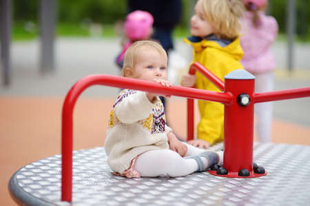 Toddler girl having fun on outdoor playground. Preschooler brother rides younger sister on carousel. Friendship of siblings. Spring / summer / autumn active sport leisure for kids. Activities for children