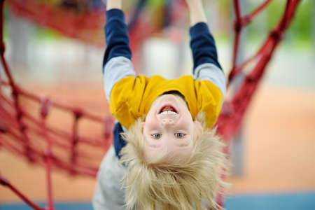 Cute perky preschooler boy having fun on outdoor playground. Spring / summer / autumn active sport leisure for kids. Outdoor activities for family with children.