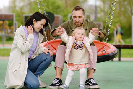 Toddler girl having fun on outdoor playground. Young parents is teaching his little daughter to walk. First step of baby. Happy parenthood.
