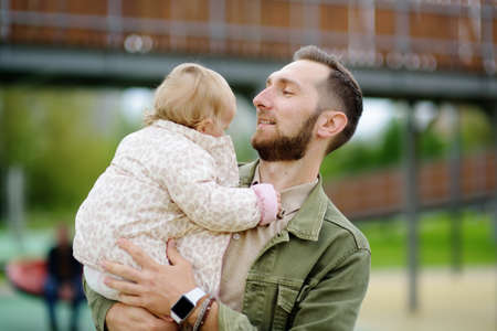 Cute toddler girl having fun on outdoor playground. Young father playing with his little daughter. Spring / summer / autumn active leisure for family with kids. Happy parenthood.
