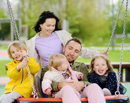 Merry family with three little children having fun on outdoor playground. Young parents rides daughters on swing. Spring / summer / autumn active leisure for family with kids. Happy parenthood.