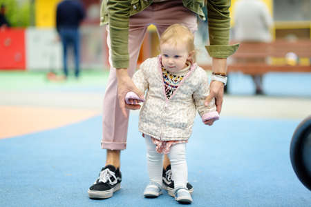 Cute toddler girl having fun on outdoor playground. Young father is teaching his little daughter to walk. First step of baby. Walking for family with little kids. Happy parenthood. Stockfoto