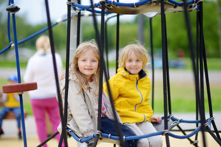 Two children having fun on playground. Spring / summer / autumn active sport leisure for kids. Outdoor activity for preschoolers. Friendship of sibling. Equipment for playground and park of entertainments