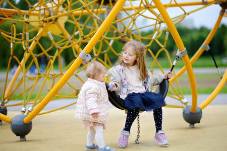 Two cute child having fun on outdoor playground. Spring / summer / autumn active sport leisure for kids. Outdoor activity for baby and preschooler. Friendship of sibling. Sisters. Stockfoto
