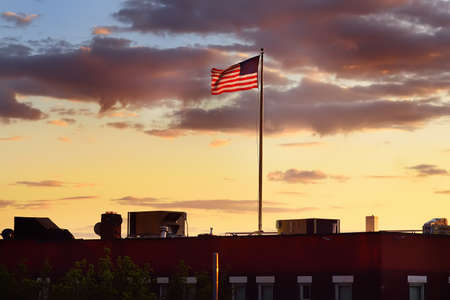 Flag of USA waving on roof top of building on background of summer sunset sky. The fourth of July is Day of Independence of United States of America.