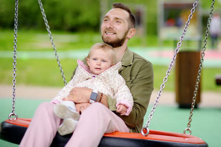 Toddler girl having fun on outdoor playground. Young father rides daughter on swing. Spring / summer / autumn active leisure for family with little kids. Happy parenthood.