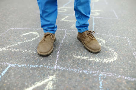 Close-up of little boy's legs and hopscotch drawn on asphalt. Child playing hopscotch game on playground on spring day. Outdoors activities for children.