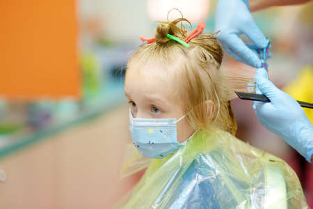 Preschooler boy wearing facemask getting haircut during epidemic. Barbershops opened after lockdown. Children hairdresser with professional tools - comb and scissors. Cutting hair for kids Stockfoto
