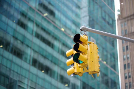 Yellow Traffic Light on background of skyscrapers, Manhattan, New York, USA. Green stop signal.