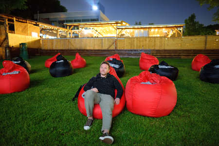 Mature man laying on pillow on grass and watching movie at outdoor cinema in public park. Perfect spending evening or weekend time in open air. Leisure and entertainment for urban people at summer Stockfoto