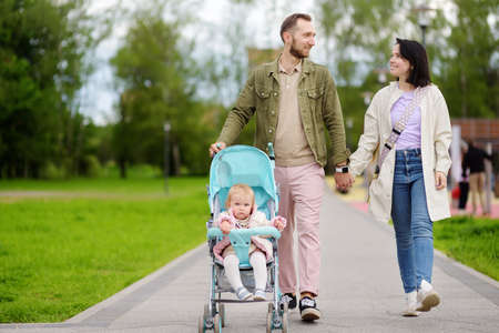 Adorable toddler girl is riding into baby stroller during walk with her young loving parents. Active leisure and walking for family with little kids. Happy parenthood.