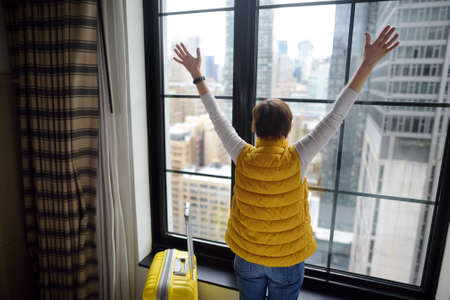 Traveler with suitcase looks and admires of amazing view the skyscrapers of Manhattan outside window. Woman tourist stayed in hotel room in New York. Tourism and travel in USA. Booking apartment. Stockfoto