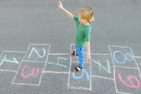 Little boy jumping by hopscotch drawn on asphalt. Child playing hopscotch game on playground on spring day. Top view. Outdoors activities for children. Stockfoto