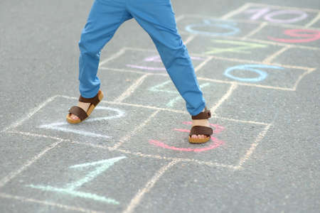 Little boy's legs and hopscotch drawn on asphalt. Child playing hopscotch game on playground on spring day. Outdoors activities for children. Stockfoto