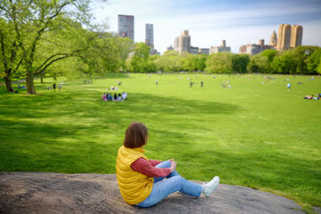 Young woman sitting on large stone in Central Park in New York on sunny spring day. Sheep meadows are lovely place for rest, relax and picnic of local and tourists. Sightseeing of NYC.