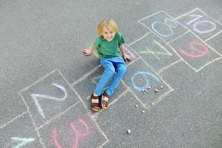 Little boy sitting on hopscotch drawn on asphalt. Child playing hopscotch game on playground on spring day. Top view. Outdoors activities for children.