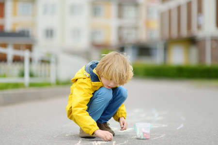 Little kid boy drawing hopscotch with colored chalk on asphalt. Child playing hopscotch game on playground outdoors on a spring day. Outdoor activities for children.