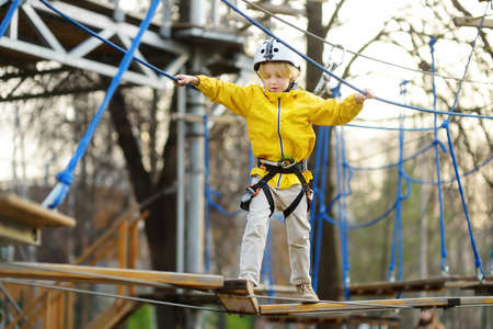 Little boy having fun in Adventure Park for children amoung ropes, stairs, bridges. Outdoor climbing adventure playground in public park. Activity entertainment for family with kids Stockfoto