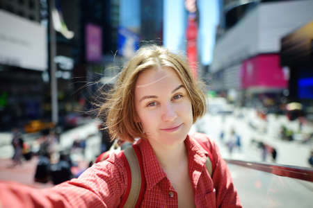 Beautiful young woman tourist taking selfie on Times Square on sunny summer day, downtown Manhattan. Famous street of New York City. Sightseeing of nyc. Stockfoto