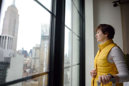 Woman tourist stays in hotel room in New York. Traveler admires of view the Empire State Building and skyscrapers of Manhattan outside the window. Tourism in the USA.