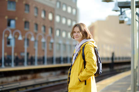 Beautiful young woman is waiting for a train on a platform in the New York subway. Transport of NYC, USA. Tourism and travel in NY.