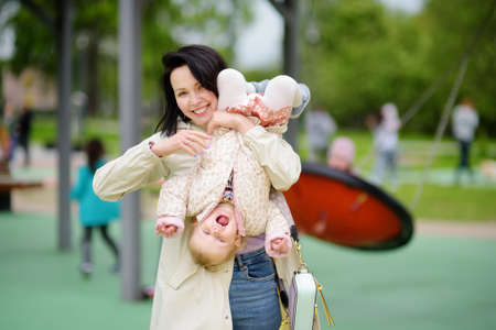 Toddler girl having fun on outdoor playground. Merry young mother swinging her little daughter. Outside active leisure for family with kids. Happy motherhood.
