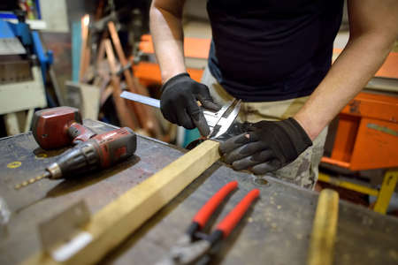 Metalwork craftsman working with metal at workshop. Man using caliper. Do it yourself. Small local business. Stockfoto
