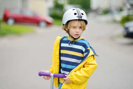 Little boy in safety helmet is riding scooter. Child is bored lonely without friends. Quality protect equipments for safety kids on street of city.