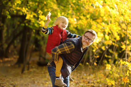 Little boy and his father having fun during stroll in the forest on sunny autumn day. The father rides the child on own back. Quality family time in the fresh air. Hiking with kids.